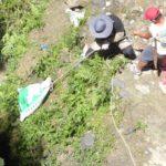 Hauling the bundled trash upslope by rope